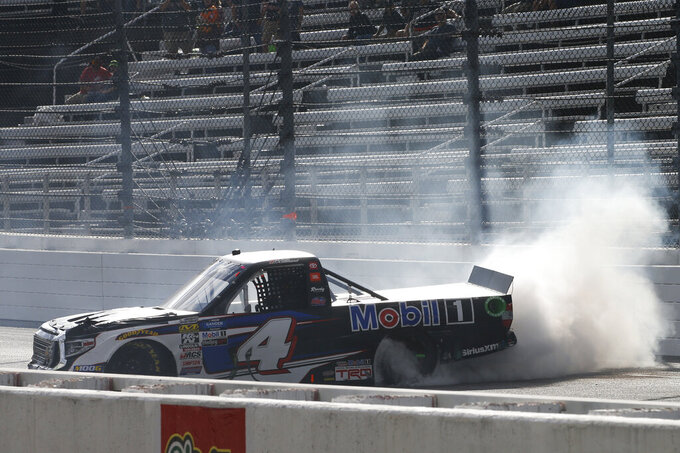 Todd Gilliland (4) does a burnout as he celebrates winning the NASCAR Truck Series race at Martinsville Speedway in Martinsville, Va., Saturday, Oct. 26, 2019, (AP Photo/Steve Helber)