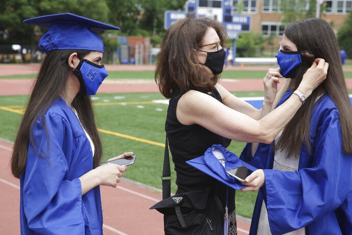 Ellen Gesner, center, helps her daughters Rachel, left, and Julia Gesner get ready for their graduation ceremony at Millburn High School in Millburn, N.J., Wednesday, July 8, 2020. This week New Jersey saw the resumption of youth day camps, in-person summer school and school graduation ceremonies, capped at 500 people and required to be outside. (AP Photo/Seth Wenig)