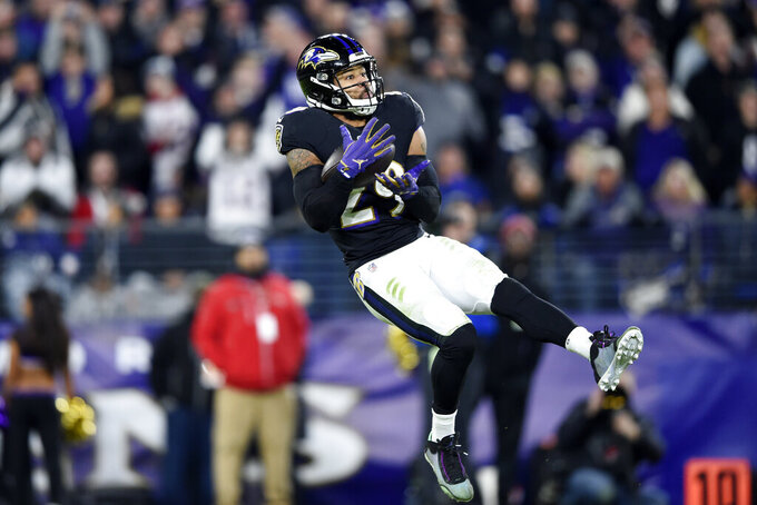 Baltimore Ravens safety Earl Thomas III intercepts a pass from New England Patriots quarterback Tom Brady during the second half of an NFL football game, Sunday, Nov. 3, 2019, in Baltimore. (AP Photo/Gail Burton)