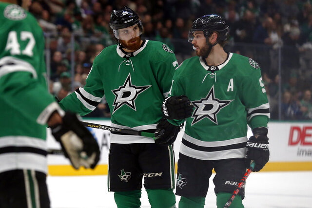 Dallas Stars defenseman Stephen Johns, left, talks with Dallas Stars center Tyler Seguin, right, during a break in the action in the second period of an NHL hockey game against the Tampa Bay Lightning in Dallas, Monday, Jan. 27, 2020. (AP Photo/Ray Carlin)