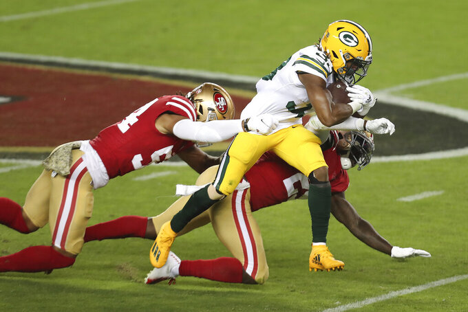 Green Bay Packers running back Aaron Jones, center, runs against San Francisco 49ers middle linebacker Fred Warner, left, and strong safety Jaquiski Tartt during the first half of an NFL football game in Santa Clara, Calif., Thursday, Nov. 5, 2020. (AP Photo/Jed Jacobsohn)