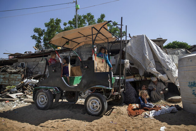 Palestinian children play on a cart outside their house in a slum on the outskirts of Khan Younis Refugee Camp, in the southern Gaza Strip, Monday, June 1, 2020. (AP Photo/Khalil Hamra)
