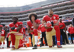 FILE - In this Oct. 2, 2016, file photo, from left, San Francisco 49ers outside linebacker Eli Harold, quarterback Colin Kaepernick and safety Eric Reid kneel during the national anthem before an NFL football game against the Dallas Cowboys in Santa Clara, Calif. When Colin Kaepernick took a knee during the national anthem to take a stand against police brutality, racial injustice and social inequality, he was vilified by people who considered it an offense against the country, the flag and the military. Nearly four years later, it seems more people are starting to side with Kaepernick's peaceful protest and now are calling out those who don't understand the intent behind his action. (AP Photo/Marcio Jose Sanchez, File)