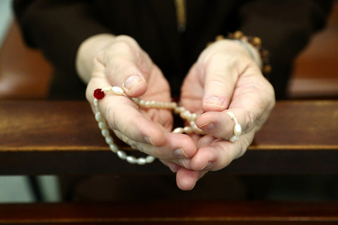 Sister Mary Carol Kardell, of the Felician Sisters of North America, prays with rosary beads during morning Mass at St. Anne Home in Greensburg, Pa., on Thursday, March 25, 2021. Communities of Catholic nuns are absorbing devastating losses from outbreaks of the coronavirus. The Felician Sisters lost 21 of their own, in four U.S. convents, a remarkable blow for a community of about 450 women.  (AP Photo/Jessie Wardarski)