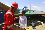 FILE - In this Aug. 1, 2018 file photo, a Tunisian Red Crescent volunteer, left, speaks with a migrant aboard the ship