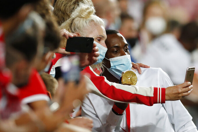 Benfica and Portugal triple jumper Pedro Pablo Pichardo, right, poses with Benfica fans and his Tokyo 2020 Olympics gold medal during halftime of the Champions League third qualifying round, 2nd leg, soccer match between Benfica and Spartak Moskva at the Luz stadium in Lisbon, Tuesday, Aug. 10, 2021. (AP Photo/Armando Franca)