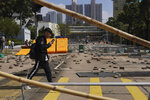 People walk by a road scattered with bricks and barricades by pro-democracy protesters outside the Hong Kong Baptist University, in Hong Kong, Wednesday, Nov. 13, 2019. Police increased security around Hong Kong and its university campuses as they brace for more violence after sharp clashes overnight with anti-government protesters. (AP Photo/Vincent Yu)