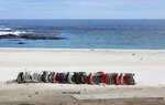 Stacked beach chairs lay on the closed beach in Camps Bay, Cape Town, South Africa Tuesday, Dec. 29, 2020. South African President Cyril Ramaphosa has declared the wearing of masks compulsory and has reimposed a ban on the sales of alcohol and ordered the closure of all bars and beaches as part of new restrictions to help the country battle a resurgence of the coronavirus, including a new variant. (AP Photo/Nardus Engelbrecht)