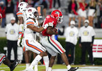 Georgia running back Zamir White (3) scores a touchdown next to Auburn linebacker Cam Riley (35) during the first half of an NCAA college football game Saturday, Oct. 3, 2020, in Athens, Ga. (AP Photo/Brynn Anderson)