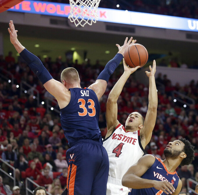 Virginia's Jack Salt (33) and Braxton Key, right, defend against North Carolina State's Jericole Hellems (4) during the first half of an NCAA college basketball game in Raleigh, N.C., Tuesday, Jan. 29, 2019. (AP Photo/Gerry Broome)