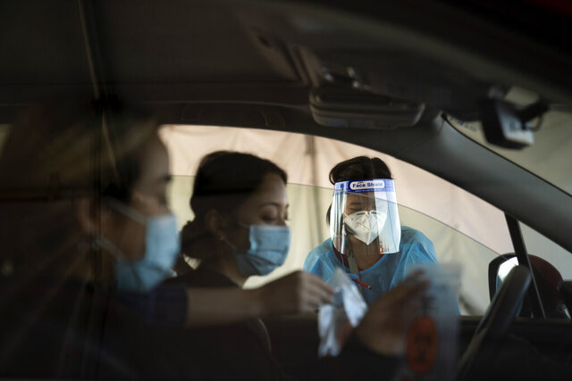 Medical assistant Linh Nguyen assists two women with COVID-19 testing at a testing site set up at the OC Fairgrounds in Costa Mesa, Calif., Monday, Nov. 16, 2020. (AP Photo/Jae C. Hong)