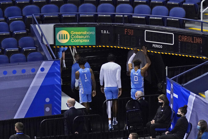 North Carolina guard Leaky Black (1) and teammates guard Anthony Harris (0) and forward Sterling Manley, center, leave the court after their 69-66 loss to Florida State in the semifinal round of the Atlantic Coast Conference tournament in Greensboro, N.C., Friday, March 12, 2021. (AP Photo/Gerry Broome)