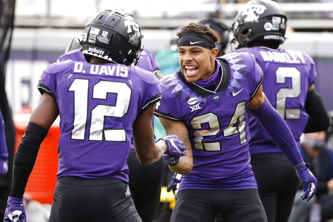 TCU wide receiver Derius Davis (12) and TCU safety Ar'Darius Washington (24) celebrate Davis' touchdown catch against Oklahoma State during the second half of an NCAA college football game Saturday, Dec. 5, 2020, in Fort Worth, Texas. TCU won 29-22. (AP Photo/Ron Jenkins)