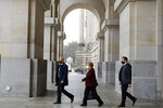 German Chancellor Angela Merkel, center, leaves the Reichstag building after a parliament session about German government's policies to combat the spread of the coronavirus and COVID-19 disease at the parliament Bundestag, in Berlin, Germany, Thursday, Nov. 26, 2020. Merkel and the country's 16 state governors have agreed to extend a partial shutdown well into December in an effort to further reduce the rate of coronavirus infections ahead of the Christmas period. (AP Photo/Markus Schreiber)