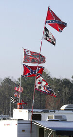 FILE - In this March 18, 2005, file photo, Confederate stars and bars flags fly on = poles attached to campers at Atlanta Motor Speedway in Hampton, Ga. NASCAR has a checkered racial history, from a long-time affinity for Confederate flags among the fan base to a driver losing his job just this season for casually uttering a racial epitaph.(AP Photo/Ric Feld, File)