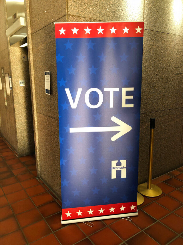 In this Jan. 9, 2020 photo, a sign points the way to the early voting station that has already been set up at the Hennepin County Government Center in downtown Minneapolis in preparation for the start of early voting on Friday, Jan. 17, in Minnesota's March 3 presidential primary. (AP Photo/Steve Karnowski)