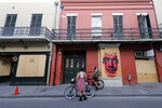 A couple on bicycles stop in front of shuttered businesses impacted by the coronavirus epidemic, on Royal St, in the French Quarter of New Orleans, Tuesday, May 12, 2020. Attempts to curb the spread of COVID-19 have visited a kind of triple economic whammy on the state.   (AP Photo/Gerald Herbert)