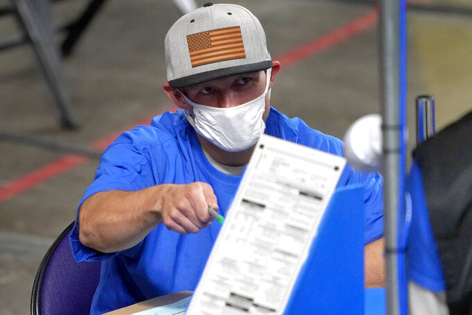 FILE - In this May 6, 2021 file photo, Maricopa County ballots cast in the 2020 general election are examined and recounted by contractors working for Florida-based company, Cyber Ninjas at Veterans Memorial Coliseum in Phoenix. On Friday, Aug. 6, 2021, The Associated Press reported on stories circulating online incorrectly asserting a state-by-state analysis of votes for President Joe Biden in the 2020 election suggests there was election fraud. But the report, which based its claims on assumptions related to voting and registration trends, provided no proof of fraud. (AP Photo/Matt York, Pool)