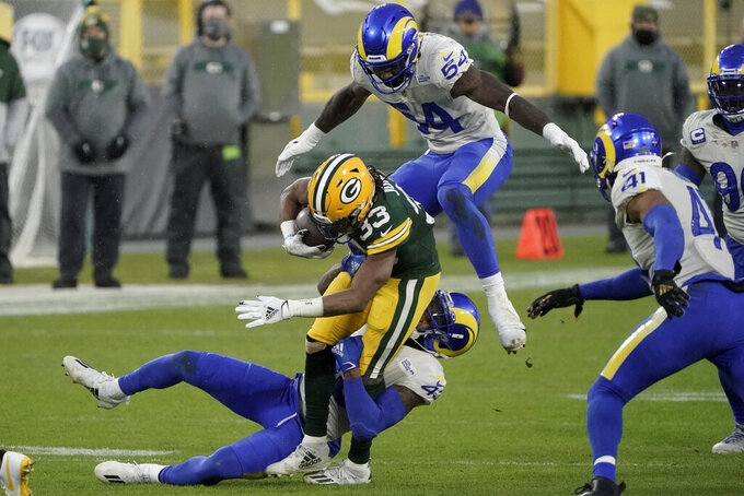 Los Angeles Rams' Leonard Floyd (54) leaps over Green Bay Packers' Aaron Jones (33) as he is tackled by Rams' Nick Scott during the first half of an NFL divisional playoff football game, Saturday, Jan. 16, 2021, in Green Bay, Wis. (AP Photo/Morry Gash)