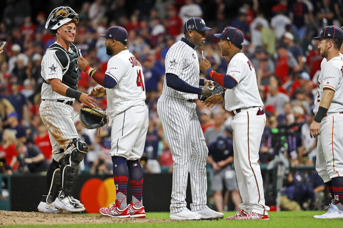 Members of the American League squad celebrate their 4-3 victory over the National League in the MLB baseball All-Star Game, Tuesday, July 9, 2019, in Cleveland. (AP Photo/John Minchillo)