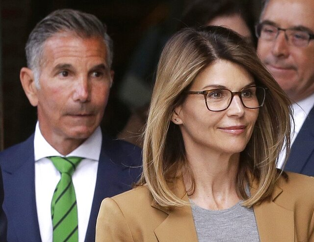 FILE - In this April 3, 2019, file photo, actress Lori Loughlin, front, and her husband, clothing designer Mossimo Giannulli, left, depart federal court in Boston. Lawyers for Loughlin and Giannulli said Wednesday, Feb. 26, 2020 that new evidence shows the couple is innocent of charges that they bribed their daughters' way into the University of Southern California.  (AP Photo/Steven Senne, File)