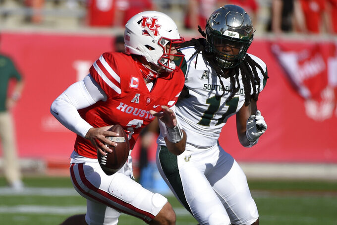 Houston quarterback Clayton Tune, left, scrambles as South Florida linebacker Dwayne Boyles defends during the first half of an NCAA college football game, Saturday, Nov. 14, 2020, in Houston. (AP Photo/Eric Christian Smith)