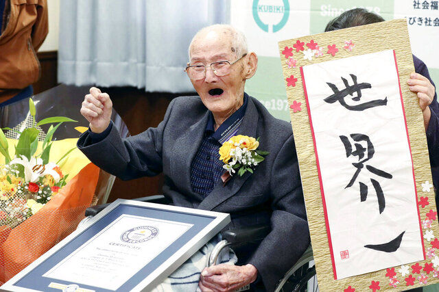 FILE - In this Feb. 12, 2020, file photo, Chitetsu Watanabe, 112, poses next to the calligraphy he wrote after being awarded as the world's oldest living male by Guinness World Records, in Joetsu, Niigata prefecture, northern Japan. The Japanese man who received his certificate as the world's oldest man with a raised fist and big smiles earlier this month has died at 112. Guinness World Records confirmed Tuesday, Feb. 25, 2020 he had died Sunday. (Kyodo News via AP, File)