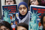 Demonstrators listen to speakers during a rally outside the U.S. 4th Circuit Court of Appeals Tuesday Jan 28, 2020, in Richmond, Va.  President Donald Trump's travel ban on travelers from predominantly Muslim countries is going back before a federal appeals court.   On Tuesday, the 4th U.S. Circuit Court of Appeals in Richmond will hear arguments in three lawsuits filed by U.S. citizens and permanent residents whose relatives have been unable to enter the U.S. because of the ban.  (AP Photo/Steve Helber)
