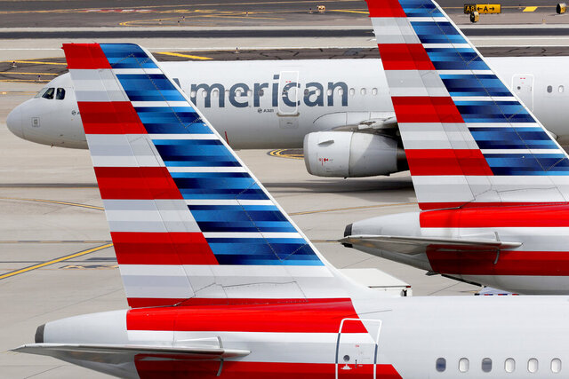 FILE - In this Wednesday, March 25, 2020, file photo, American Airlines jets sit idly at their gates as a jet arrives at Sky Harbor International Airport in Phoenix. American Airlines will let employees wear Black Lives Matter pins on their uniforms, calling it a matter of equality and not politics, the airline said Tuesday, Sept. 8, 2020. (AP Photo/Matt York, File)