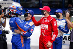Scott Dixon, front left, of New Zealand, celebrates with teammates, Tony Kanaan, left center, of Brazil, Marcus Ericsson, right, center, of Sweden, and Alex Palou of Spain, after winning the pole during qualifications for the Indianapolis 500 auto race at Indianapolis Motor Speedway in Indianapolis, Sunday, May 23, 2021. (AP Photo/Michael Conroy)