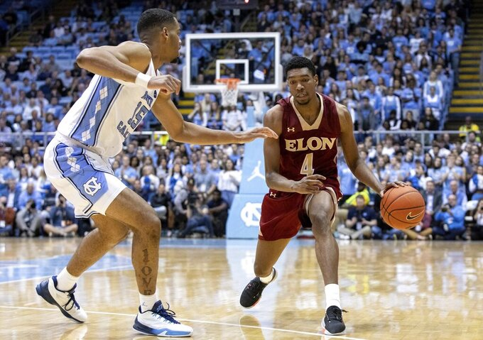 Elon's Marcus Sheffield II (4) handles the ball as North Carolina's Garrison Brooks (15) defends during the second half of an NCAA college basketball game in Chapel Hill, N.C., Wednesday, Nov. 20, 2019. (AP Photo/Ben McKeown)