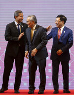 From left, Singapore Foreign Minister Vivian Balakrishnan, Thailand Foreign Minister Don Pramudwinai, and Vietnam Foreign Minister Pham Binh Minh greet each other after posing for a group photo during the Association of Southeast Asian Nations (ASEAN) Foreign Ministers' meeting in Bangkok, Thailand, Saturday, June 22, 2019. (AP Photo/Gemunu Amarasinghe)