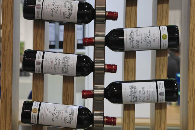 FILE - In this Feb.10, 2020 file photo, red wine bottles of the region of Medoc, western France, are displayed at the wine fair in Paris. French wine exporters are warning that they'll take a billion-euro hit in 2021 from the latest ratcheting-up of punitive tariffs between the United States and Europe in a trade row over aircraft subsidies. (AP Photo/Michel Euler, File)