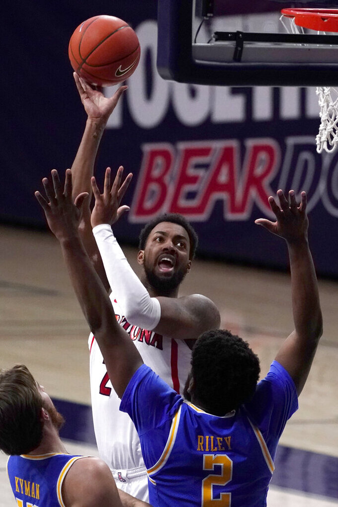 Arizona forward Jordan Brown (21) shoots over UCLA's Jake Kyman and Cody Riley (2) during the first half of an NCAA college basketball game Saturday, Jan. 9, 2021, in Tucson, Ariz. (AP Photo/Rick Scuteri)