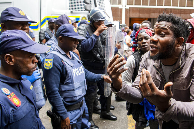 FILE — In this Wednesday, Oct. 30, 2019 file photo police clash with protesters outside the U.N. refugee agency's offices in Cape Town, South Africa.  The Home Affairs Ministry says that, as of Jan. 1 2020, South Africa can strip refugees of their status if they engage in any political activity related to their home countries.(AP Photo, File)