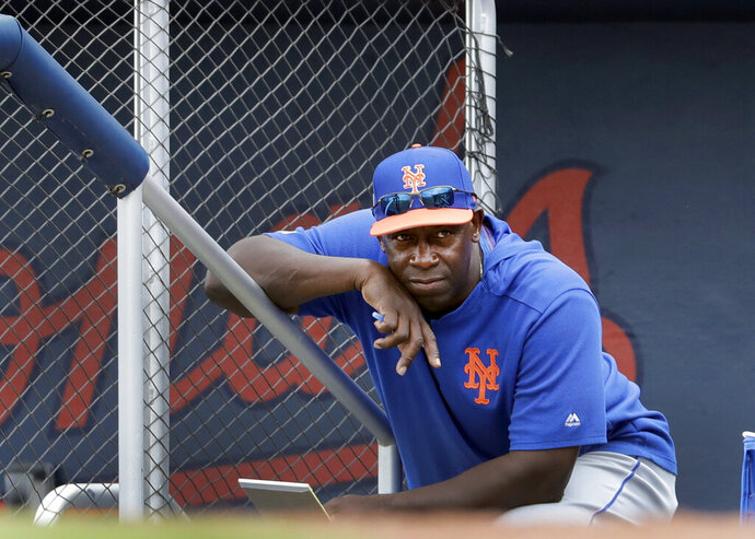 FILE - In this Monday, Feb. 25, 2019 file photo, New York Mets hitting coach Chili Davis watches from the top of the dugout steps during the fifth inning of an exhibition spring training baseball game against the Houston Astros in West Palm Beach, Fla. Hitting coach Chili Davis will keep on working remotely when the New York Mets open summer training camp Friday, July 3, 2020. (AP Photo/Jeff Roberson, File)