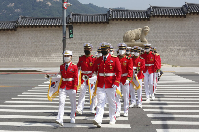 Members of the South Korean military band wearing face masks to help protect against the spread of the new coronavirus cross a road during an event to commemorate the upcoming 70th anniversary of the Korean War, in Seoul, South Korea, Monday, June 15, 2020. (AP Photo/Ahn Young-joon)