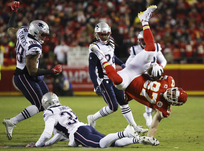 Kansas City Chiefs tight end Travis Kelce (87) spins in the air as he is tackled by New England Patriots defensive back Jonathan Jones (31) during the first half of the AFC Championship NFL football game, Sunday, Jan. 20, 2019, in Kansas City, Mo. (AP Photo/Elise Amendola)