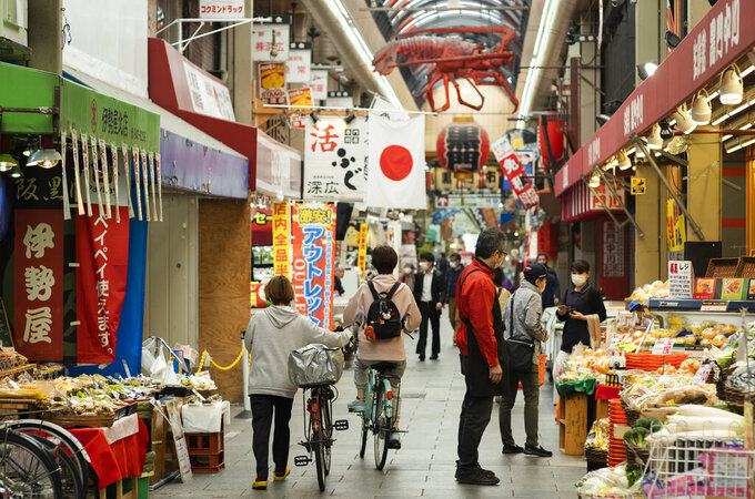 People wearing face masks to help curb the spread of the coronavirus shop around at the Kuromon Ichiba market in Osaka, western Japan, Tuesday, April 20, 2021. (AP Photo/Hiro Komae)