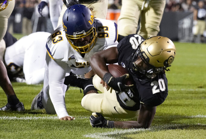Colorado running back Deion Smith, front, falls into the end zone past Northern Colorado defensive lineman Tava Finau for a touchdown during the second half of an NCAA college football game Friday, Sept. 3, 2021, in Boulder, Colo. Colorado won 35-7. (AP Photo/David Zalubowski)