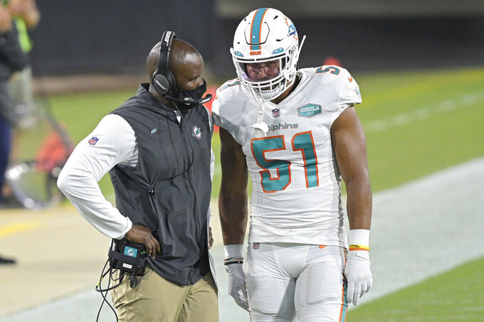 "FILE  - In this Thursday, Sept. 24, 2020, file photo, Miami Dolphins head coach Brian Flores, left, talks with outside linebacker Kamu Grugier-Hill (51) on the sidelines during the first half of an NFL football game against the Jacksonville Jaguars, in Jacksonville, Fla. The Dolphins and Seattle Seahawks play on Sunday, Oct. 4. Everything has changed for Flores since the 2015 Super Bowl when he substituted Malcolm Butler, who made a game-saving interception of Russell Wilson to help New England edge Seattle. ""That stuff is in the past,"" Flores said. ""Can't help us now."" Then Patriots' linebackers coach, Flores is now in his second year as the Miami Dolphins' head coach.  (AP Photo/Phelan M. Ebenhack, File)"