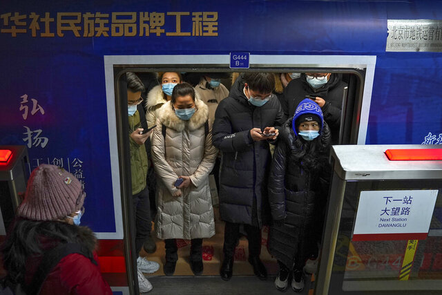 Commuters wearing face masks to help curb the spread of the coronavirus crowd inside a subway train during a rush hour in Beijing, Tuesday, Jan. 5, 2021. Wary of another wave of infections, China is urging tens of millions of migrant workers to stay put during next month's Lunar New Year holiday, usually the world's largest annual human migration. (AP Photo/Andy Wong)