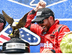 Ross Chastain celebrates in victory lane as teammates spray champagne after winning a NASCAR Truck Series auto race, Saturday, July 27, 2019, in Long Pond, Pa. (AP Photo/Derik Hamilton)