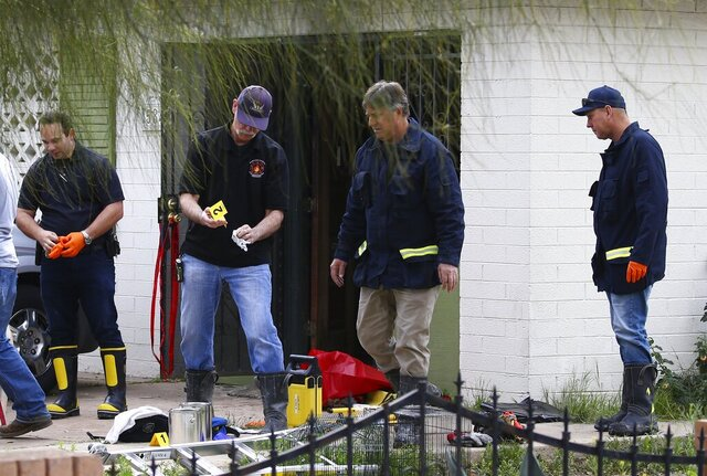 Phoenix Fire Department investigators look through evidence at a home where skeletal remains were found Wednesday, Jan. 29, 2020, in Phoenix. The remains have been found at a house where authorities previously removed at least one child as part of a child abuse investigation in which both parents of that child were in custody, police said Wednesday. (AP Photo/Ross D. Franklin)