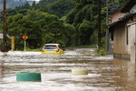 A car is stuck in a flooded road by heavy rain in Yatsushiro, Kumamoto prefecture, southwestern Japan, Saturday, July 4, 2020. The Japan Meteorological Agency raised the heavy rain warnings in many parts of the prefectures to the highest level shortly before 5 a.m. It was the first time for the agency to do so in the two prefectures, Kumamoto and Kagoshima. (Kyodo News via AP)