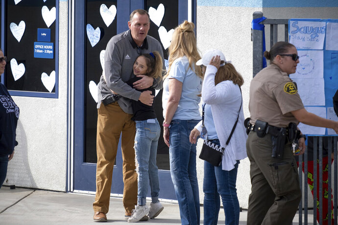 Saugus high principal Vince Ferry gives hugs and welcomes students back on campus Tuesday, Nov. 19, 2019. Students were allowed back to collect their belongings left behind after the tragic shooting last Thursday. Classes will resume at the high school on Dec. 2. (David Crane/The Orange County Register via AP)