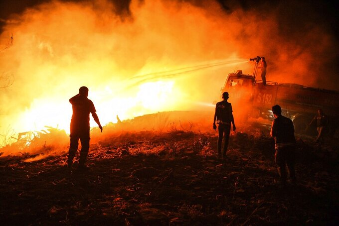 Firefighters and Local villagers try to get the fire under control in Kirli village near the town of Manavgat, in Antalya province, Turkey, early Friday July 30, 2021. The fire that continued all night could not be brought under control and people living in the village started to evacuate. Wildfires are common in Turkey's Mediterranean and Aegean regions during the arid summer months, although some previous forest fires have been blamed on arson. (AP Photo)