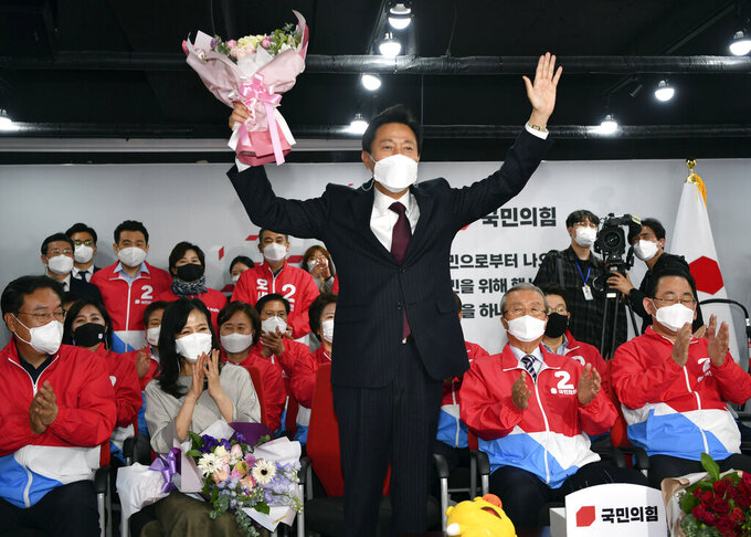 Oh Se-hoon, candidate of the main opposition People Power Party, holds flowers while watching televisions broadcasting the counting for the Seoul mayoral by-election at party headquarters in Seoul, South Korea, Thursday, April 8, 2021. (Song Kyung-Seok/Pool Photo via AP)