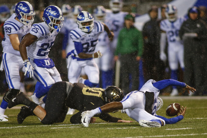 Duke quarterback Quentin Harris, right, tries to recover a fumble against Wake Forest defensive lineman Rondell Bothroyd in the first half of an NCAA college football game in Winston-Salem, N.C., Saturday, Nov. 23, 2019. Wake Forest recovered the football. (AP Photo/Nell Redmond)
