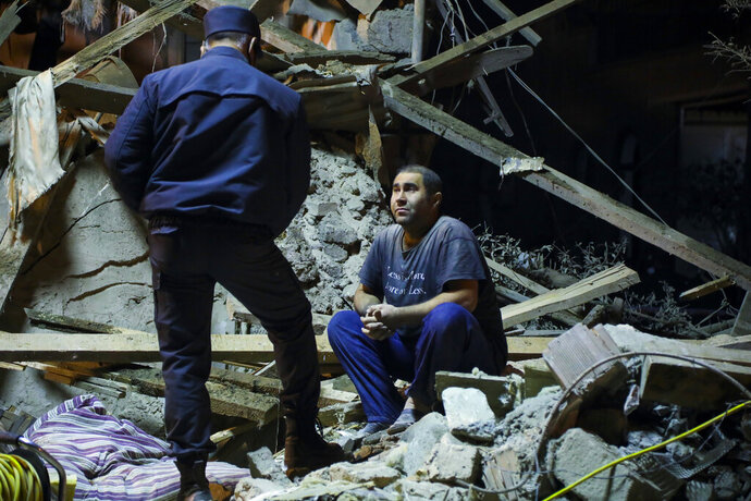 An Azerbaijan's policeman, left, speaks to a man siting at his destroyed house in a residential area that was hit by rocket fire overnight by Armenian forces, early Saturday, Oct. 17, 2020, in Ganja, Azerbaijan's second largest city, near the border with Armenia. (AP Photo/Aziz Karimov)